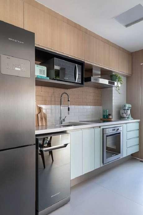 32. Cozinha moderna decorada com armário aéreo de madeira e gabinete em verde pastel – Foto: Marina Carvalho