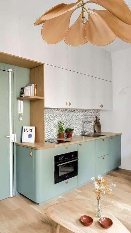 51. Cozinha retrô decorada com armários brancos e em verde pastel com puxadores dourados – Foto: Futurist Architecture
