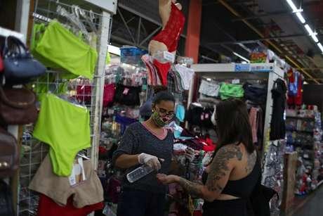 Vendedora higieniza mão de cliente em loja de mercado popular do Rio de Janeiro 17/06/2020 REUTERS/Pilar Olivares