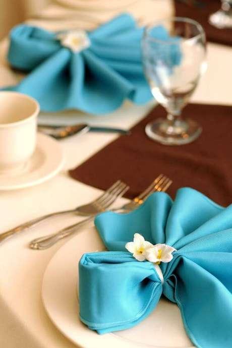 13. Como dobrar guardanapo de tecido azul com flores decorativas – Via: Pinterest