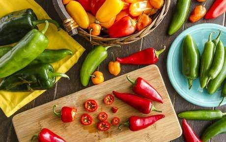 Vários tipos de pimentas sobre uma mesa, tábua e dentro de potes