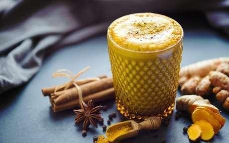 Copo de leite dourado com canela e gengibre ao lado
