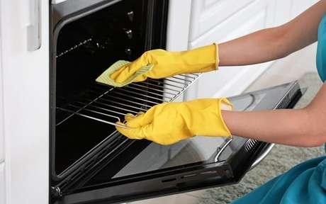 Pessoa limpando forno com pano e usando luvas amarelas