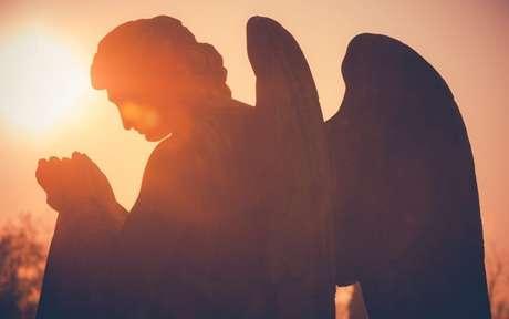 Foto de uma estátua de um anjo contraluz