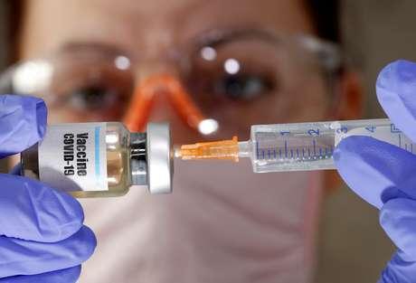 """Mulher segura frasco com rótulo """"Vacina Covid-19"""" e seringa em foto de ilustração 10/04/2020 REUTERS/Dado Ruvic"""