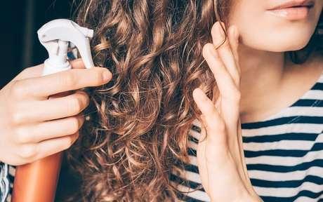 Mulher aplicando produto no cabelo cacheado