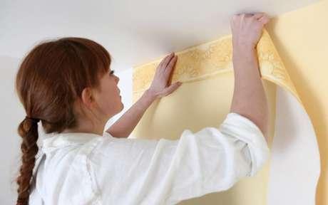Mulher aplicando papel de parede