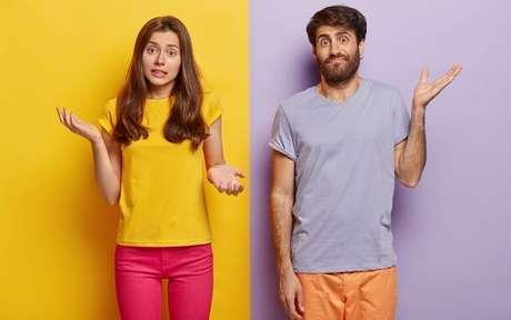 Homem e mulher em um fundo de cores diferentes, fazendo sinal de confusão