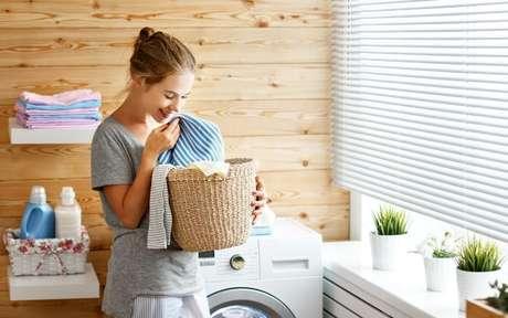 Mulher cheirando uma peça de roupa em uma lavanderia