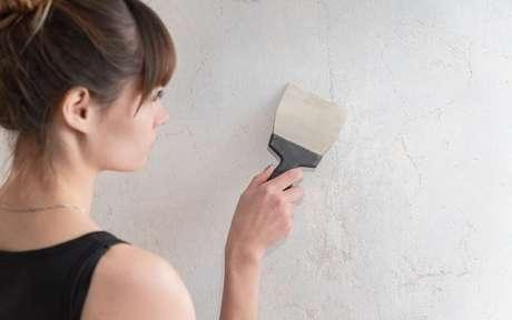 Mulher com espátula arrumando a parede