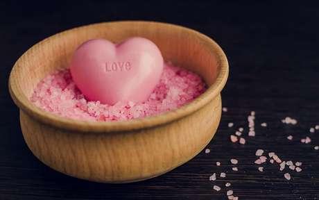 Sabonete em forma de coração dentro de um recipiente com pedras rosas