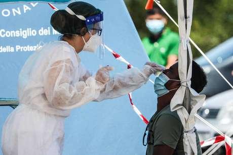 Operadora sanitária submete imigrante bengalês a exame de Covid-19 em Roma, na Itália, em 17 de julho