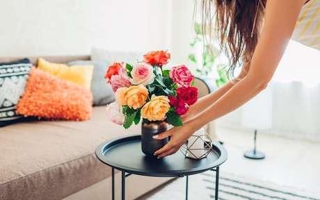 Mulher arrumando um arranjo de flores na sala