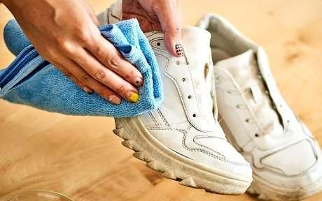 Mulher limpando um tênis com pano