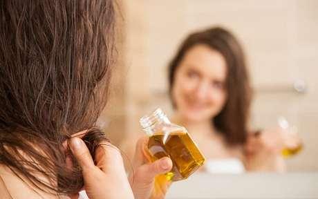 Mulher hidratando o cabelo com óleos naturais