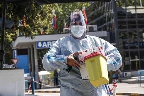 Operadores sanitários durante operação de testagem em passageiros da Romênia em rodoviária em Roma, capital da Itália