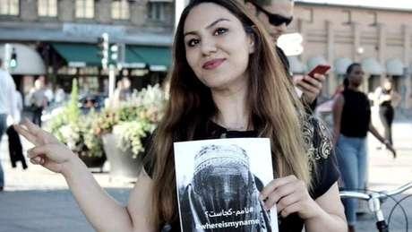 A ativista Sahar Samet mostra cartaz da campanha WhereIsMyName?