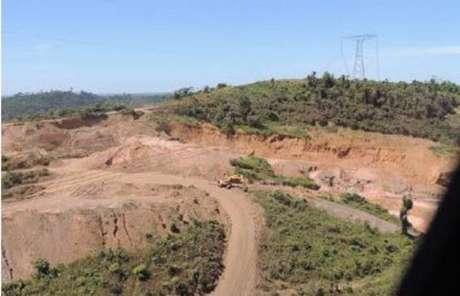 Área próxima da base de torre de transmissão de energia com sinais de atividade de garimpo.