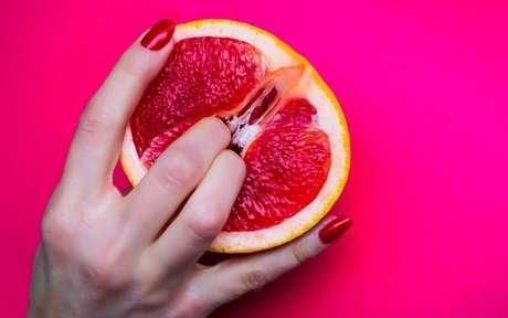 Mulher com os dedos dentro de uma laranja