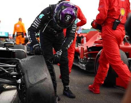 Lewis Hamilton olha o pneu dianteiro esquerdo furado que quase custou a vitória em Silverstone