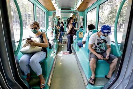 Passageiros de máscaras em VLT em Milão, na Itália
