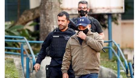 Queiroz conduzido à prisão em foto de junho; no mês seguinte, o ministro do STJ João Otávio de Noronha concedeu ao réu prisão domiciliar