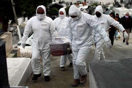 Funcionários de cemitério de Nova Iguaçu (RJ) enterram homem de 62 anos vítima da Covid-19 16/07/2020  REUTERS/Pilar Olivares