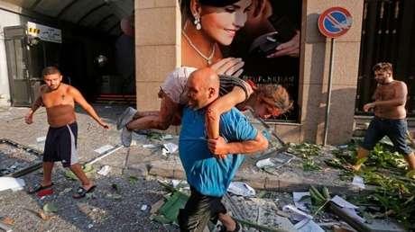 Homem retira mulher ferida de escombros em Beirute