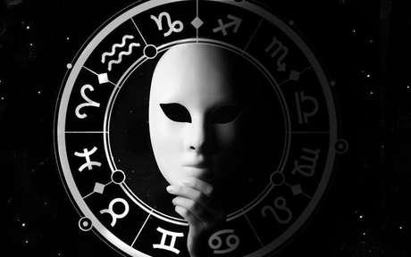 Máscara branca com fundo preto e, ao redor, os símbolos dos signos