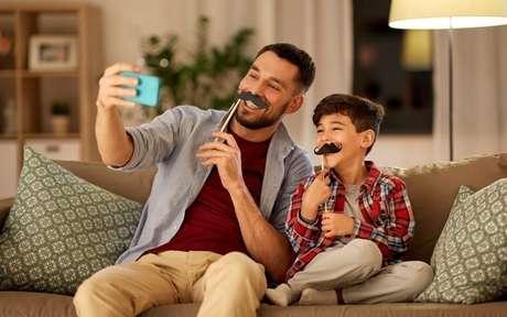 Homem ao lado do filho, sentados em um sofá, ambos com um bigode de papel, tirando uma foto