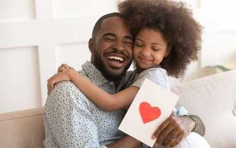 Menina abraçando um homem, enquanto ele segura um cartão com um desenho de um coração