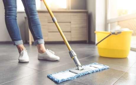 Pessoa limpando o piso com um rodo e uma balde