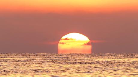 O sol pode ficar vermelho sobre o mar e com um céu laranja.