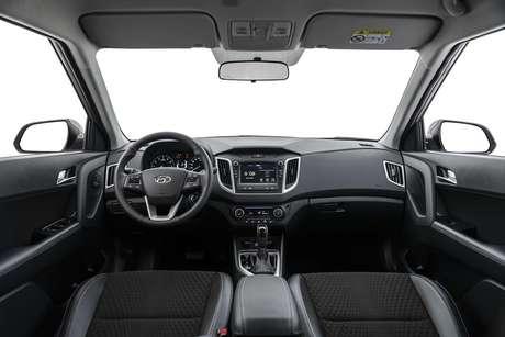 """No interior, versão tem volante de couro, ar-condicionado automático e digital, central multimídia BlueMedia 7"""" e TV Digital."""