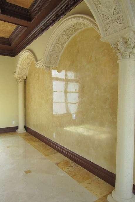 55- A parede com textura em marmorato complementa a arquitetura com arcos de gesso e forro com madeiras aparentes. Fonte: Splat Paint