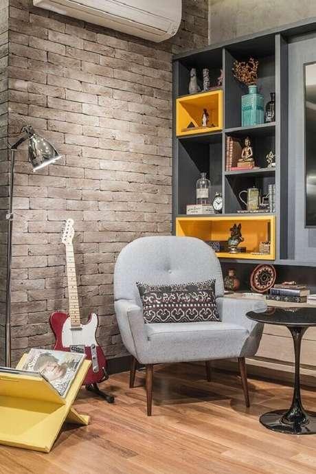 43. Poltrona decorativa cinza para sala com parede de tijolinho e estante de nichos planejada – Foto: Casa de Valentina