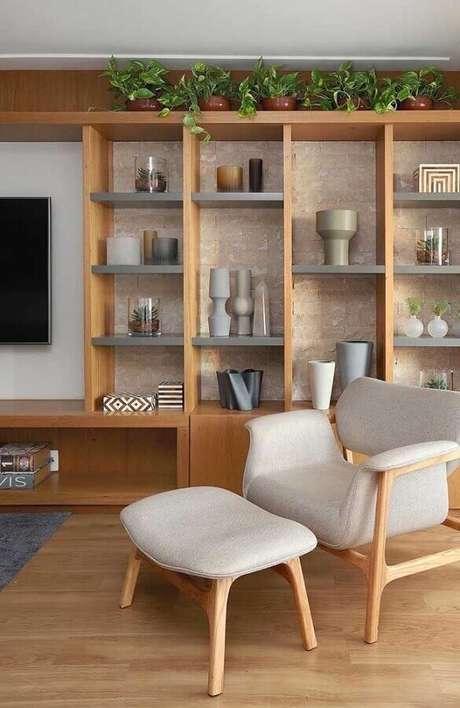 46. Sala decorada com estante de madeira planejada e poltrona decorativa com puff cinza – Foto: Pinterest