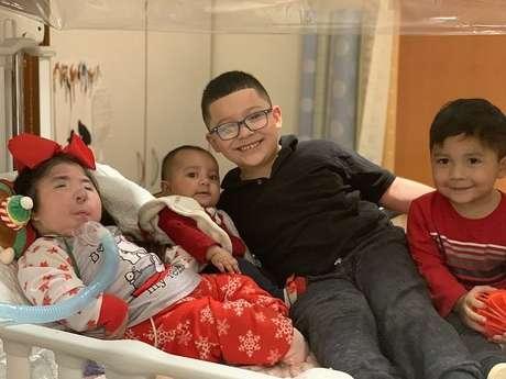 Em foto tirada antes da pandemia, Maria recebe visita dos irmãos Khloe, de quase um ano, Matthew, de sete, e Jesse, de três