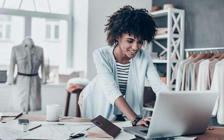 Mulher negra mexendo no computador em uma loja de roupa