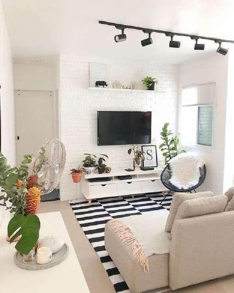12. Decoração de sala branca com TV direto na parede de tijolinho e tapete listrado – Foto: Casa de Valentina