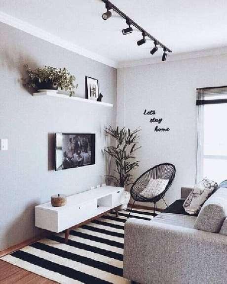 13. Decoração simples para sala cinza e branca com tapete listrado e TV direto na parede – Foto: Pinterest