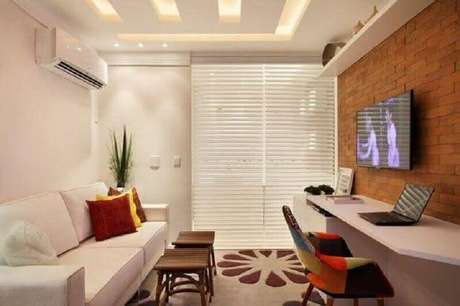 16. TV na parede da sala pequena decorada com sofá branco e cadeira colorida – Foto: Pinterest