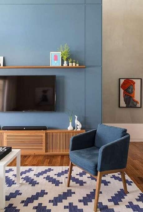 22. Decoração de sala com TV na parede azul com rack de madeira – Foto: Simplichique