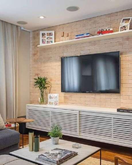 23. TV direto na parede de tijolinho para sala com rack suspenso – Foto: Casa de Valentina