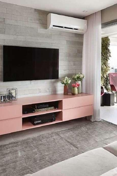 25. Decoração de sala com rack cor de rosa e TV direto na parede – Foto: Eu Capricho