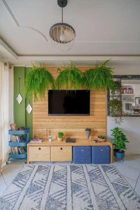 26. TV na parede decoração de sala com revestimento de madeira e samambaias suspensas – Foto: Diycore