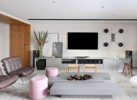 7. Decoração de sala ampla moderna com tv na parede e puffs cor de rosa – Foto: Futurist Architecture