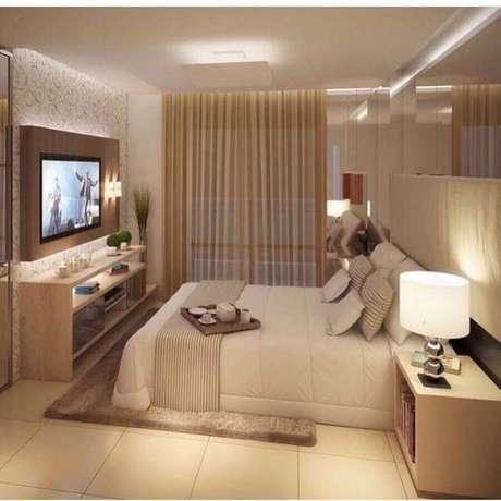6. Decoração em tons de bege com TV na parede do quarto de casal – Foto: Aprimore Decor