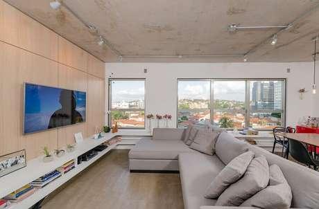 28. Sala ampla decorada com TV na parede e sofá cinza com chaise – Foto: Archdaily