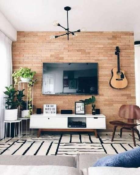 29. TV direto na parede de sala decorada com tapete preto e branco e vasos de plantas – Foto: Pinterest